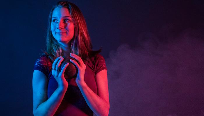 Jeune femme tenant une boule de quilles dans les mains